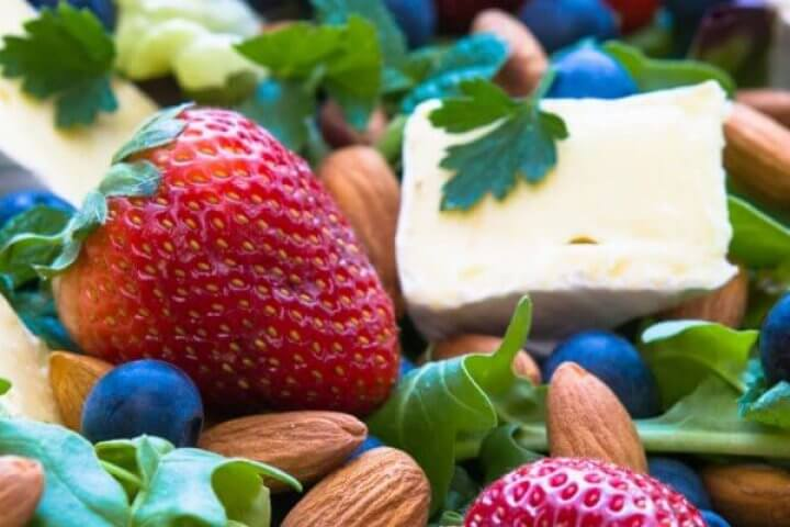 green salad with strawberries, blueberries, and almonds